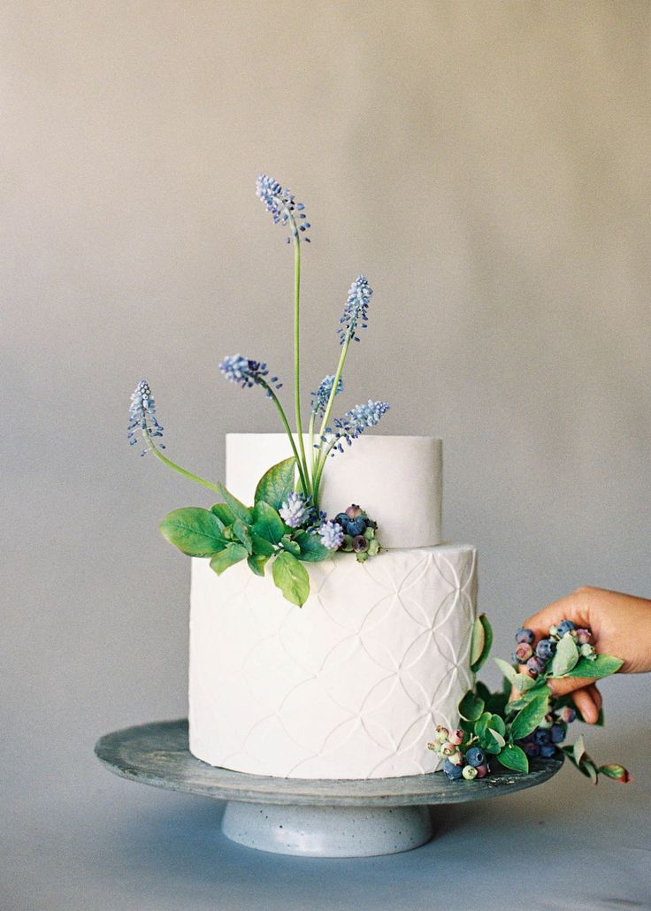 Elegantly simple wedding cake adorned with hellebores, grape hyacinth, and blueberries on the vine