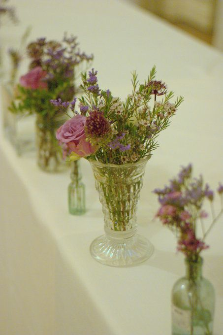 scattered glass vases Autumn style wedding flowers jam jars and vintage roses Rustic style tea stained roses