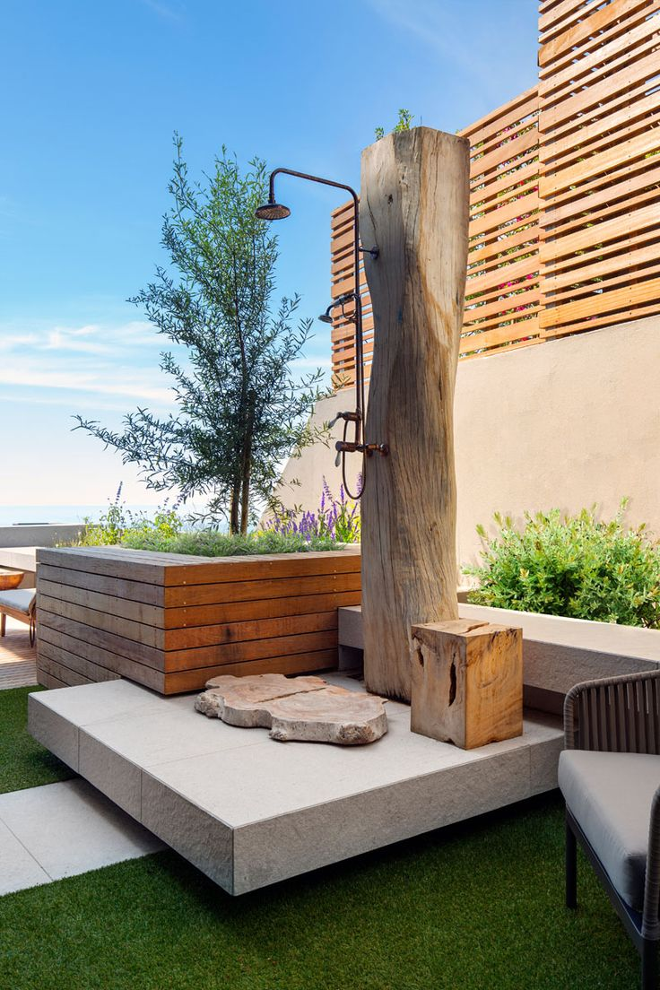 This modern outdoor shower was created from a reclaimed tree trunk and brass piping. #OutdoorShower #ModernLandscaping
