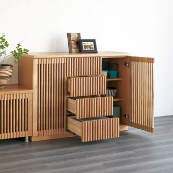 端正を極めた格子デザインで、こだわりのくつろぎ空間を演出するリビング収納シリーズ。日本国内の職人が一つひとつ手作業で丁寧に仕上げたタモ材の格子が、リビングダイニングや寝室、パーソナルルームに趣を添えます。シンプルで華やかなデザインなので、和室にも洋室にもなじみやすく、シーンを選ばずに設置できます。時を超えた美しさで多くの人を魅了する縦格子の収納家具です。