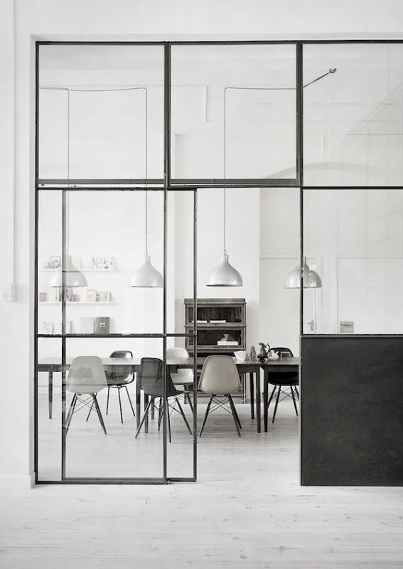 Dining area behind an industrial looking glass wall via Silver blonde