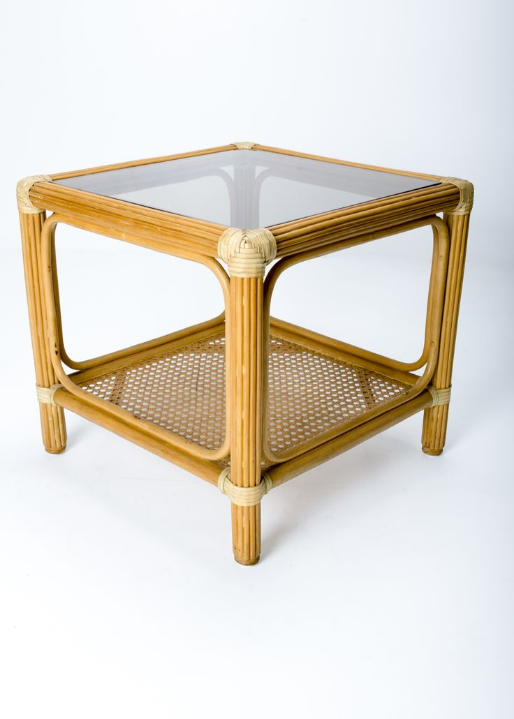 Exceptional mid-century modern side or end table in the style of John McGuire. A ratten shelf is supported by a rattan rod frame bound with rawhide and holds a new bronzed strengthed glass top. Stamped GM- Garry Masters, Queensland