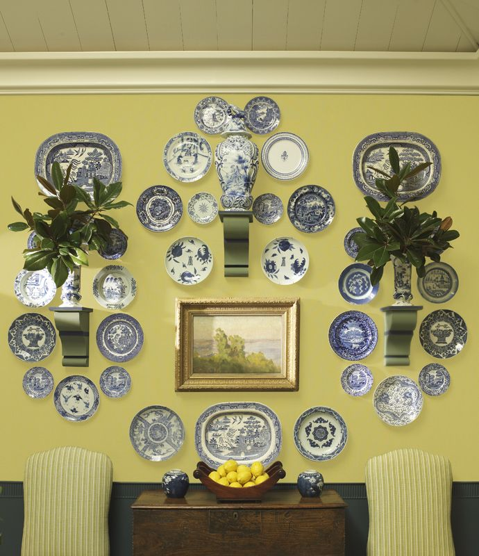 .mixing platters, plates with wall brackets and a painting breaks up the boardom of all plates on a wall.