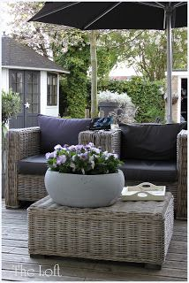 garden 'lounge' with palest wicker furniture, grey cushions and umbrella with a large stone bowl filled with pansies - how lovely! THE LOFT