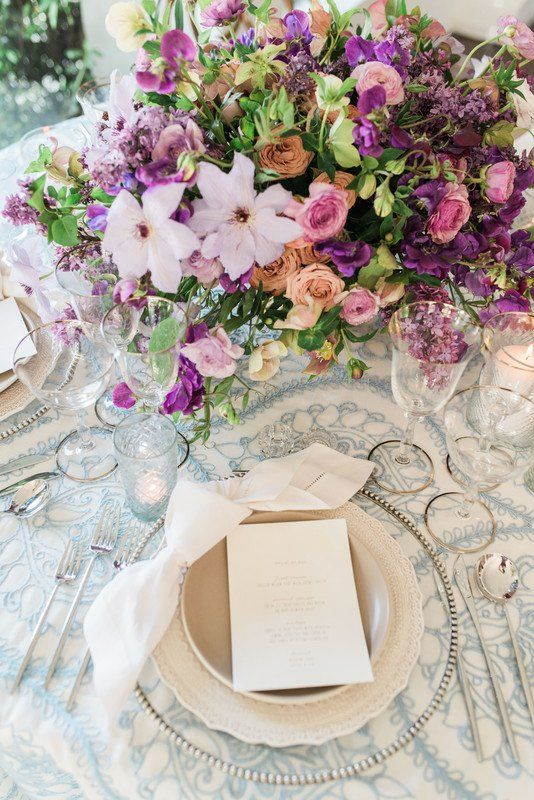 Spring wedding place setting idea - clear chargers with white menu cards and purple + pink floral centerpiece {La Tavola Fine Linen Rental}