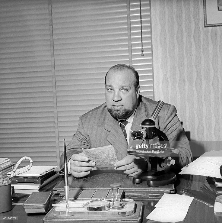 The private detective Tom Ponzi, at his desk with a letter in his hands; among the tools of the trade visible in the foreground are a microscope and a magnifying lens; the window at his back has lowered blinds. Milan (Italy), August 1963