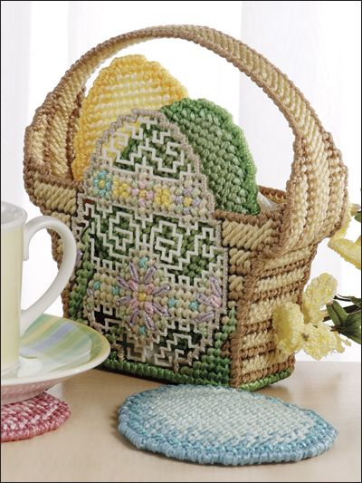 "Egg Basket Coasters    Stitch this basket holder with egg coasters for your Easter decor.    Size: Coasters: 3 3/8"" x 4 3/8"". Basket: 6"" x 5 3/4"" x 1 5/8"". Made with 7-count plastic canvas, plastic canvas yarn, metallic braid, #3 and #5 pearl cotton."