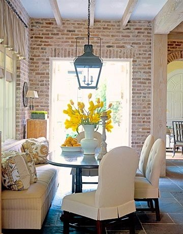 Elegant simple dining area with a fabric bench couch beige chair exposed brick yellow floral centerpiece arrangement