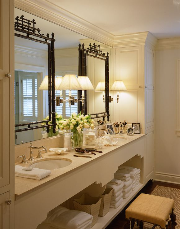Stunning master bathroom features a built-in vanity with shelf boasting his and her sinks and hook and spout faucets under black pagoda mirrors mounted on a frameless vanity mirror illuminated by swing-arm sconces with pleated shades.