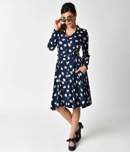 At ease in water, dears! This gorgeous navy blue shirt dress from Emily & Fin is a marvelous 1930s style silhouette for a casual stroll through the water garden. Cast in a luscious navy blue woven fabric, Paige features sweet slate blue loti floating grac