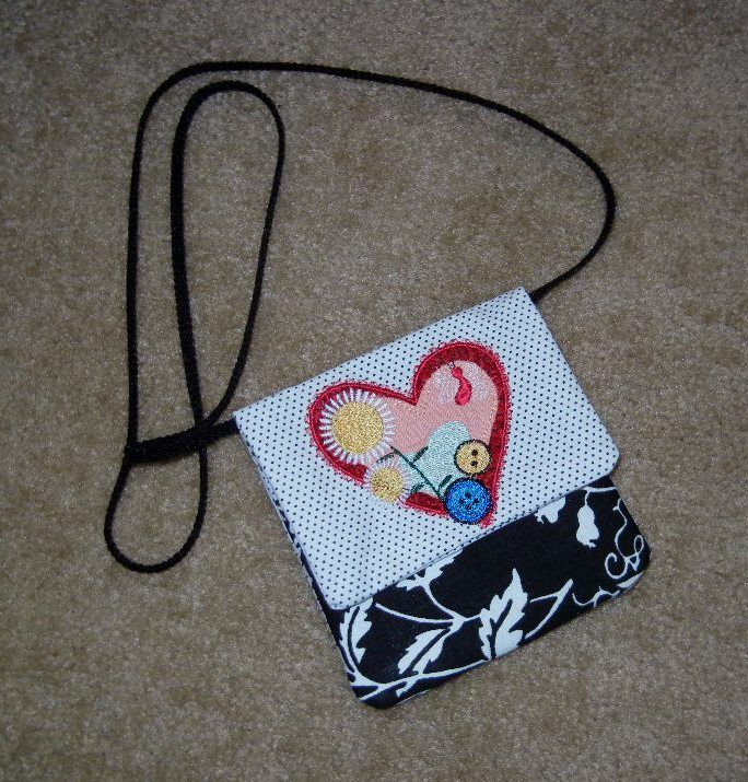NEW  Heart cell phone purse... worn across the body, this mini purse has two pockets for carrying your cell phone, small wallet, make up etc.  Ideal for when you don't want to carry a larger hand bag.  Size - 6 inches square.