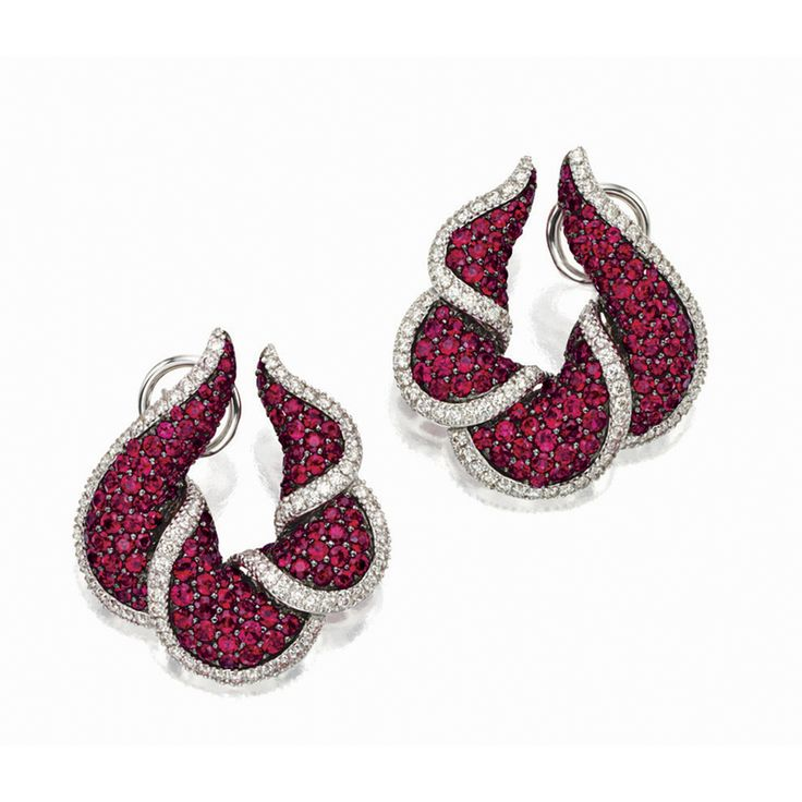 PAIR OF RUBY AND DIAMOND EAR CLIPS Each of bombé form, draped with pavé-set circular-cut ruby swirls, accentuated by brilliant-cut diamond edges, altogether the rubies weighing approximately 11.25 carats and diamonds approximately 2.35 carats, mounted in 18 karat white and blackened gold, clip and post fittings.