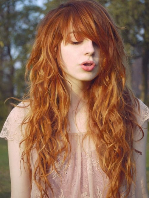 Beautiful long red curly hairstyle with bangs