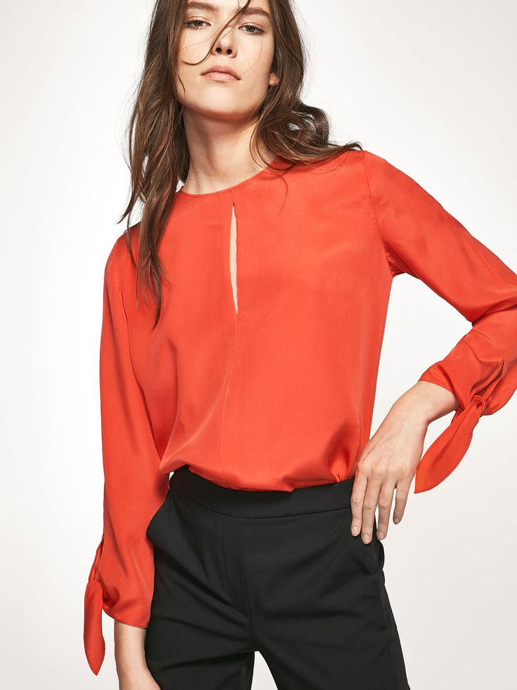 Flowing blouse with front slit detail. Made from 100% mulberry silk. Straight cut, round neck, hook and eye fastening in the back, 7/8 long sleeves with decorative tie and rounded hem.