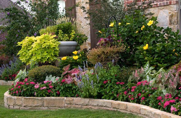 bordure de jardin en pierre délimite la pelouse et le parterre de fleurs et d'arbustes