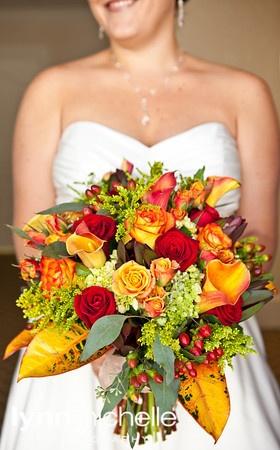 beautiful autumn theme wedding, extravagant red, yellow, and orange floral arrangement.
