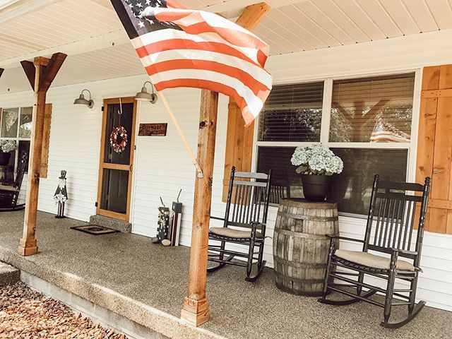 White Farmhouse Front Porch With Chunky Cedar Columns Black Cracker Barrel Rocking Chairs Whiskey Bar Summer Porch Summer Porch Decor Farmhouse Front Porches