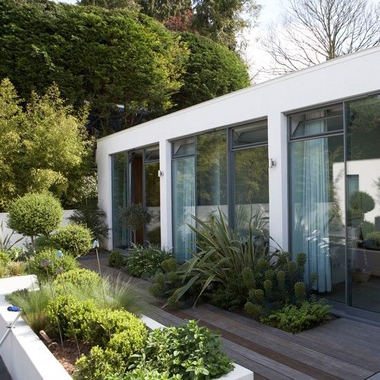 Much like its adjoining house, this modern garden is defined by clean lines and blocky shapes. Introducing different heights - from sunken plants that emerge out of the decking, to a raised white planter box that echoes the building design - creates all the drama necessary in this cool design.
