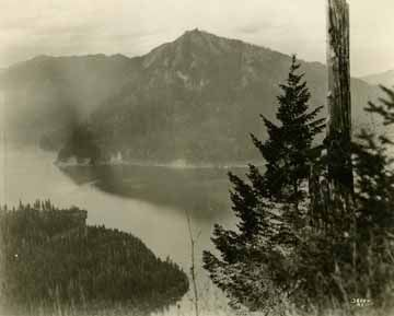 Catalog ID Number: 1943.42.36884    Object Type: print, photographic,album, photograph    Full Description:   photographic print in album, view of Lake Crescent from Mount Storm King, in Clallam County, Wa, Asahel Curtis, photographer, October 30, 1918. The image is from a series of photographs documenting work completed by the U.S. Army Spruce Production Division in preparation for the construction of a logging railroad to transport spruce logs to Fort Vancouver and other sites.