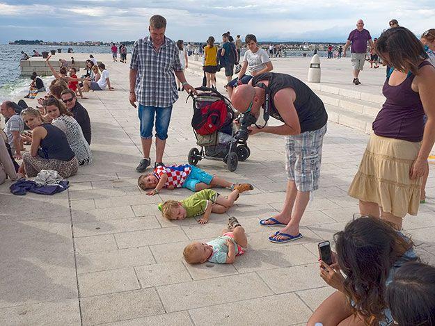 """Na Riva em Zadar, Croácia, crianças pressionam seus ouvidos sobre os canos para ouvir o """"Órgão do Mar"""". Zadar tem incorporado tubos no muro de contenção de concreto. A mágica por trás dessa instalação é causada pelo vai-e-vem da maré, que flui por uma série de túneis abaixo do nível do chão e produz uma miríade de sons poéticos. As ondas batendo contra os tubos  produz uma música que lembra baleias cantando. As pessoas no chão, ouvem extasiadas a música. Texto e fotografia: Barbara Weibel."""