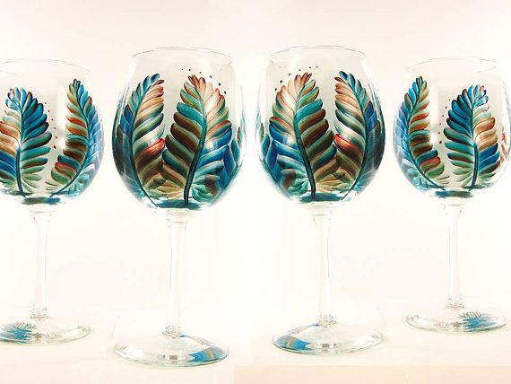 Set of 4 hand-painted wine glasses feature large feathers in rich Southwestern shades of clear deep turquoise, silver, burnished copper and Sedona red. Accent dots gracefully follow the movement and curve of the feathers. Ive painted a different feather on the base of each glass,