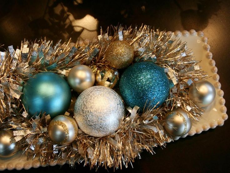Layer garland with a collection of colorful ornaments in your favorite tray to create an irresistible holiday centerpiece. Janell Beals dresses up a vintage-inspired porcelain tray with bold accessories and uses a mixture of silver, blue and gold hues for a twist on the traditional red and green.
