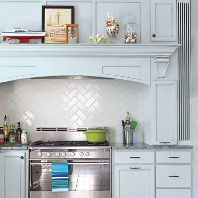 Cool blue and a white herringbone backsplash update a classic kitchen. | Photo: Julian Wass thisoldhouse.com