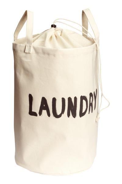 Saco para roupa suja: Saco para roupa suja em sarja de algodão cru com texto estampado. Tem duas pegas, revestimento de plástico no interior e parte superior coberta em tecido mais fino com fecho com cordão de ajuste. Medidas: 34x52 cm.
