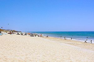Guia de Praias do Algarve   Popular Villas - À beira do mais exclusivo resort turístico do Algarve, e protegida pelo Parque Natural da Ria Formosa e das suas magníficas dunas, a praia da Quinta do Lago é uma das praias mais deslumbrantes e melhor preservadas da Europa. Esta praia oferece um extenso areal sem formações rochosas, com acesso pedonal por uma ponte de madeira que atravessa a Ria Formosa. Coordenadas de localização: GPS N 37º 1' 34.56'', W -8º 1' 31.54''
