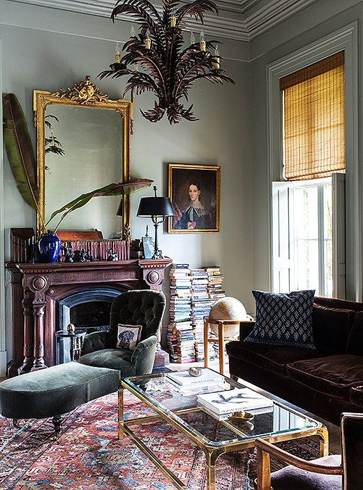 Love this dramatic and moody library filled with gold mirrors, a Persian rug and velvet seating.