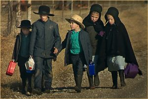 Amish walking to school. They carry their books along with a big jug of water and a small cooler with a days worth of food and snacks.