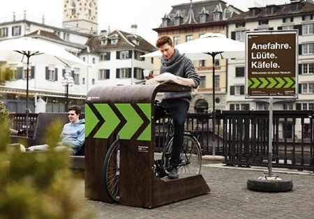 "Like the bike version of a classic drive-in restaurant that lets diners eat without leaving their car, this stand lets bikers enjoy coffee without getting off their two-wheeled rides. (The German sign in the photo says ""Drive up. Ring. Enjoy your coffee."") The Velokafi stand was designed to include a tabletop, a place to dock your bike, and side rails to rest your feet as you perch."