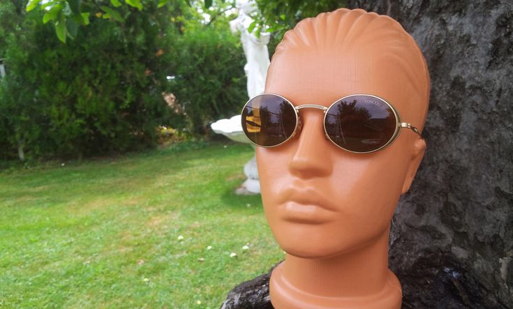 €40 This is a never worn pair of vintage matt gold tone or black or silver metal oval 1990's unisex sunglasses with side shields. They are never used frame has excellent condition. Lenses are dark amber or blue or mauve colored. Avaiable in 3 colors.