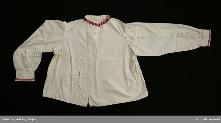"""Huvudliggaren:  """"Kvinnodräkt. a)kjortel, b)överdel, c)livstycke 'snörlif', d)förkläde, e)'hatt' med 'knitning', f)'hätta', g)'halskläde', h)'löfnål'. """"    Bilaga:  Inget utöver huvudliggaren.    Katalogkort:  Inga ytterligare uppgifter.      b. Nattröja i vit tuskaftad bomull, öppen fram, vid och rundskuren form nedtill  fram och bak.   /Inga-Lill Eliasson 2007-06-21"""