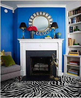 Living Room With Royal Blue Walls Grey Sofa White Fireplace A Sunburst Mirror On The Mantel Built In Bookshelves And Zebra Print Car