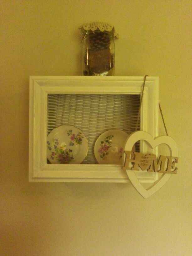 Old basket , with photo frame added and turned into a shelf.