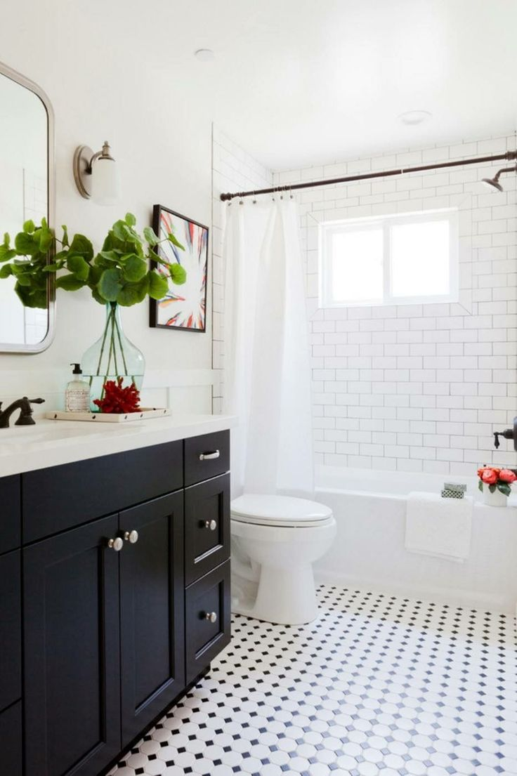 Love how fresh and modern this bathroom feels, while still highlighting timeless styles like black tuxedo cabinets, white subway tiled walls and checkered tile floors.