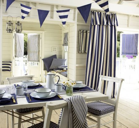 Prestigious Textiles -  Maritime Fabric Collection - Blue and white striped roman blinds and curtains, plaid seating pads, blue placemat, an...