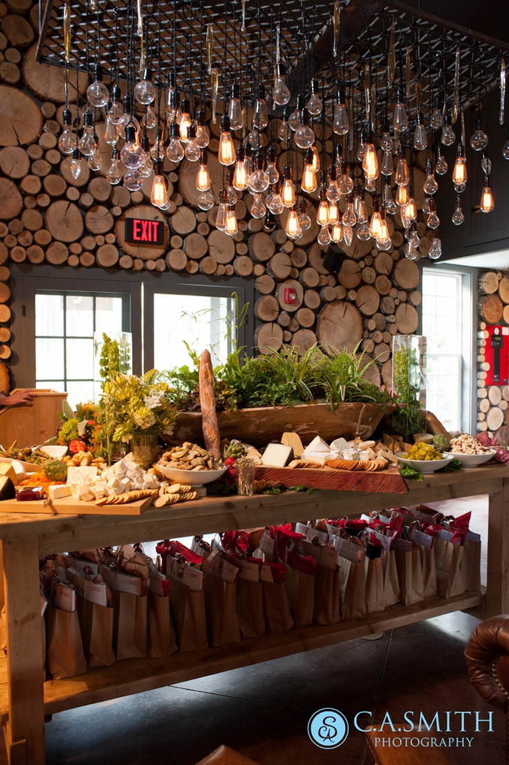 Look at that amazing wall. Love the rustic table with the plants. And all of those bulbs to make a light fixture. Wow!