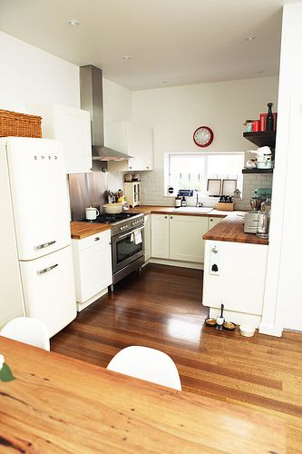 White smeg fridge (freezer on bottom), wood floors and countertops, white cabinets... stove should also be white.