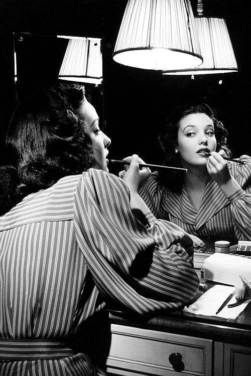 missavagardner:  Linda Darnell putting on make-up in mirror, photographed by Herbert Gehr, c. 1940s.