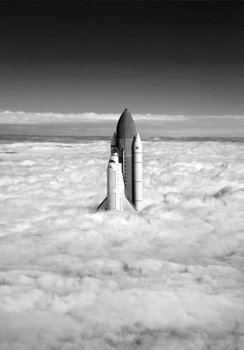 A space shuttle surrounded by clouds