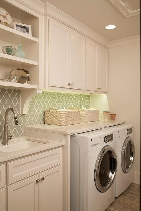 Fabulous laundry room features creamy white shaker cabinets topped with an ivory countertop fitted with a sink and satin nickel gooseneck faucet paired with a gray arabesque tiled backsplash under open shelving, A white front load washer and dryer are tucked under a countertop below creamy white shaker cabinets accented with under cabinet lighting.