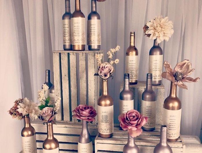plan de table mariage avec des bouteilles de vin argentée et dorées disposées autour de caisses de bois blanchis, aspect usé et petites fleurs dedans
