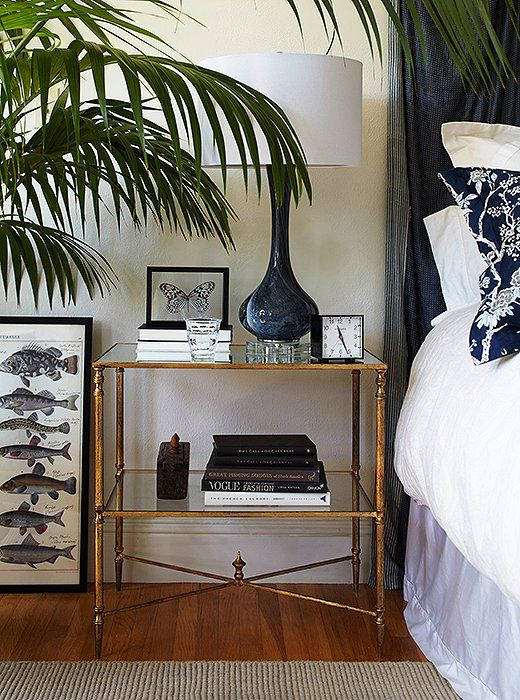 Stacie's tiered, gilded glass nightstand is visually light but offers great storage for books and other accessories.