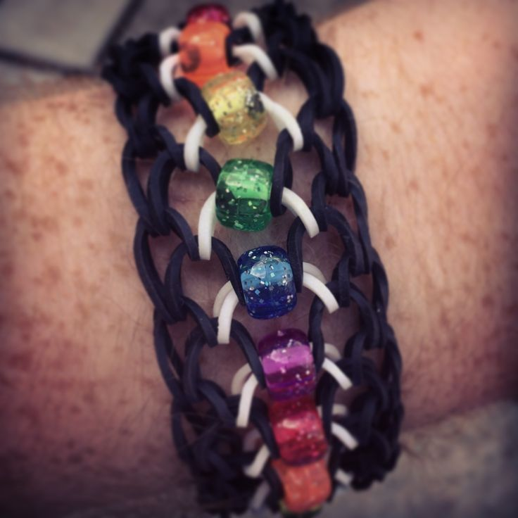 Fun with the rainbow loom and beads. It's a dragon scale cuff if you want to look it up. I just added in beads. Uses black and glow rainbow bands, as well as rainbow glitter pony beads.