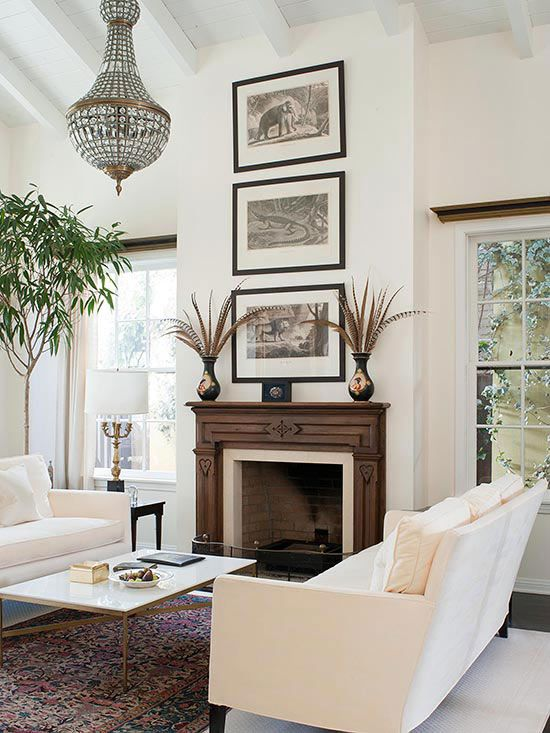Wooden Warmth..A wooden fireplace surround is unexpected in this white living room, but it adds a sense of warmth and a natural touch. The dark wood tone contrasts the white room, but gives off a calm, homey feel rather than a stark, modern look. The carvings on the sides of the fireplace and the mantel add detail and character. #fireplace #decorate