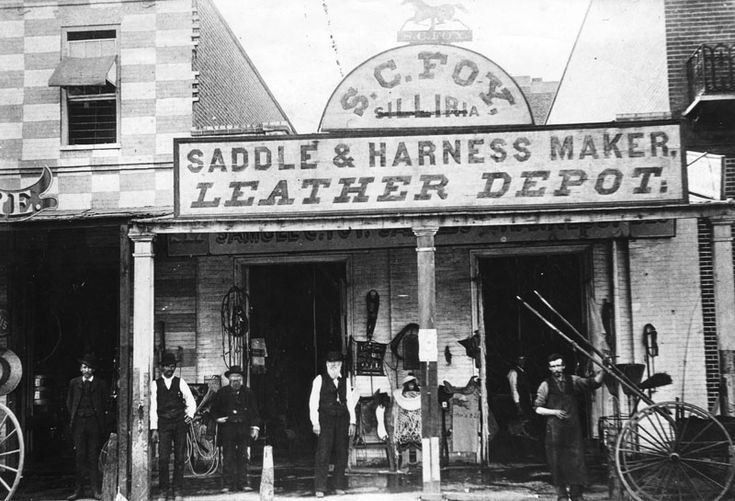 """Exterior view of S. C. Foy saddlery shop, housed in a one-story, brick building with a portico. The store sign reads """"Saddle & Harness Maker, Leather Depot"""" and has a silhouetted prancing horse on top. Tack and saddles are displayed on the front and several men are posing for the camera. Mr. Foy was the father of Mary Foy, Los Angeles's first city librarian."""