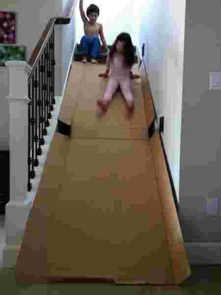 Deux enfants qui glissent sur un toboggan en carton