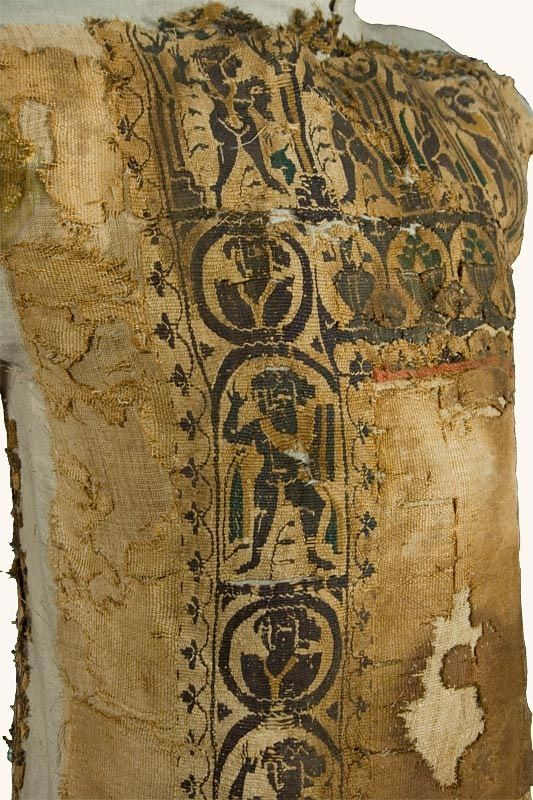 This tunic was a garment commonly worn by males in Greco-Roman civilizations. At the top of this tunic, an arcade encloses figures of dancers and warriors. Below, two vertical panels with warriors and dancers alternate with roundels amid human busts.